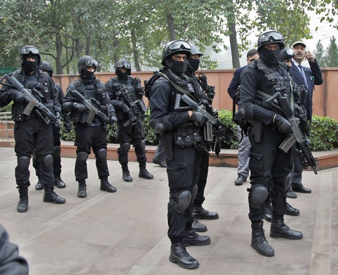 Members of India's NSG stand guard outside the Mahatma Gandhi memorial before the arrival of U.S. President Obama at Rajghat in New Delhi
